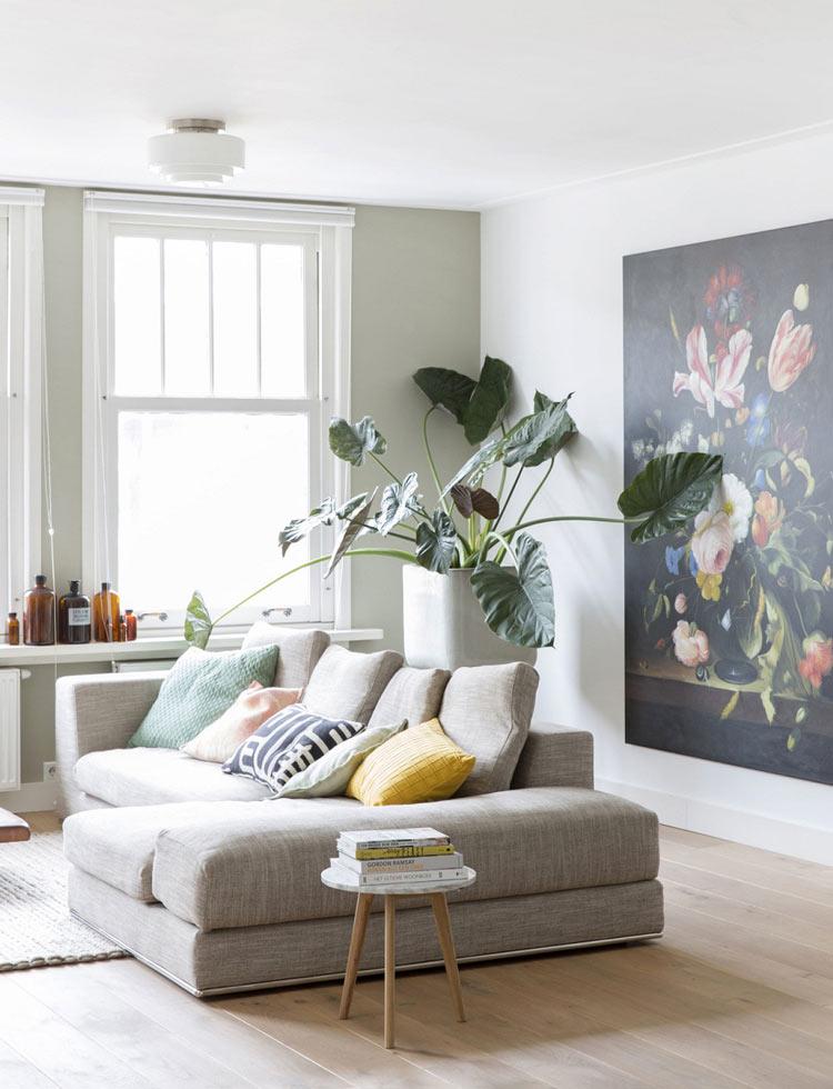 Chậu cây cảnh xanh mát đặt sau sofa giường chính là điểm nhấn cho mẫu phòng khách có tông màu trắng chủ đạo này